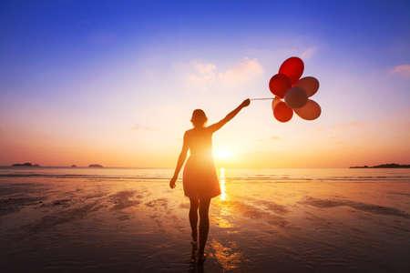 幸福概念、肯定的な感情、日没で夏のビーチを楽しむ色とりどりのバルーンと幸せな女の子