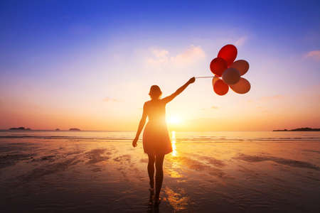 happiness concept, positive emotions, happy girl with multicolored balloons enjoying summer beach at sunset