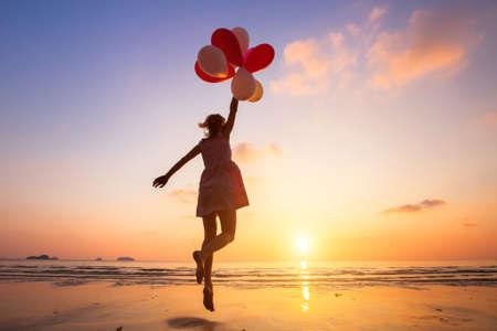 想像力、夕暮れビーチ、フライ、色とりどりの風船でジャンプ幸せな少女は、夢を追う 写真素材