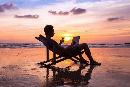 일몰, 프리랜서 작업 개념, 해외 작업 해변에서 노트북에 이메일을 읽고 성공적인 비즈니스 사람 (남자)의 실루엣
