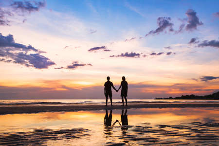 family relationships: happy family on the beach, silhouette of couple at sunset, man and woman relationships, love