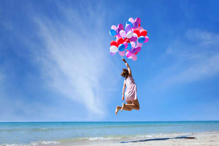 dream concept, girl flying on multicolored balloons in blue sky, imagination and creativity Foto de archivo