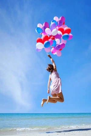 inspiration, happy people, woman flying with multicolored balloons in blue sky, creative concept