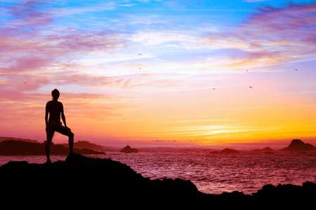Concepto de bienestar, silueta de persona disfrutando de hermosa puesta de sol con vista al mar