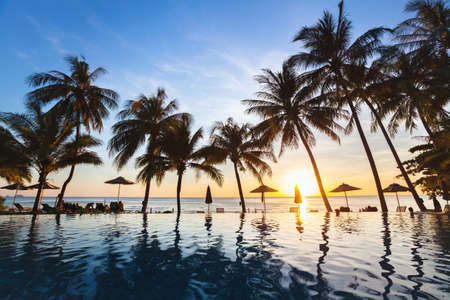 beautiful sunset tropical beach landscape of paradise island with silhouettes of palm trees, summer holidays background