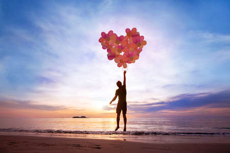 love concept, man flying with heart from balloons, fall in love Stockfoto