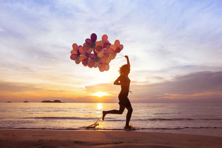 happiness concept, psychology of happy people, young woman running with multicolored balloons on the beach