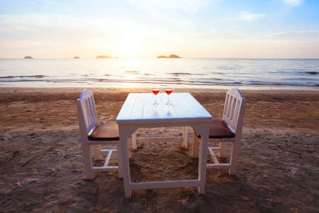 two cocktails on the table in luxury beach restaurant at sunset