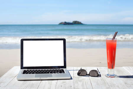 Office on the beach, laptop with empty screen, sunglasses and tropical cocktail