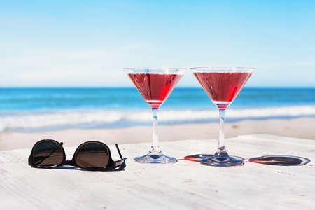 夏の休日の概念、2 つのカクテル、ビーチ テーブル、熱帯休暇のサングラス