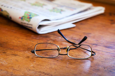 reading newspapers, close up of glasses on the wooden table