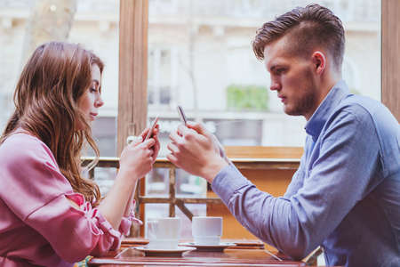 adultery: always connected, internet addiction, young couple in cafe looking at their smartphones, social network concept Stock Photo