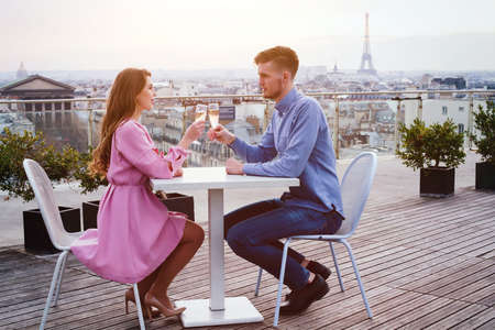 エッフェル塔のパノラマの景色とパリの豪華な屋上レストランでシャンパンを飲むカップル