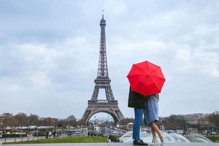 Honeymoon in Parijs, paar kussen achter rode paraplu tegen de Eiffeltoren