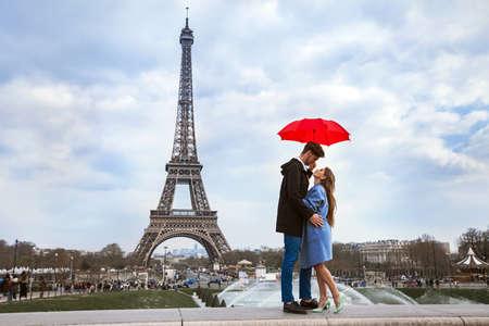 beautiful couple with umbrella near Eiffel Tower, honeymoon in Paris, romantic moment Stock Photo - 77400385
