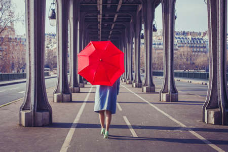 fashion woman with red umbrella walking on the street in Paris