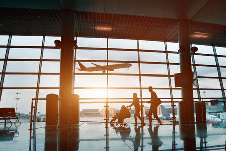 people in airport, silhouette of young family with baby traveling by plane Stockfoto