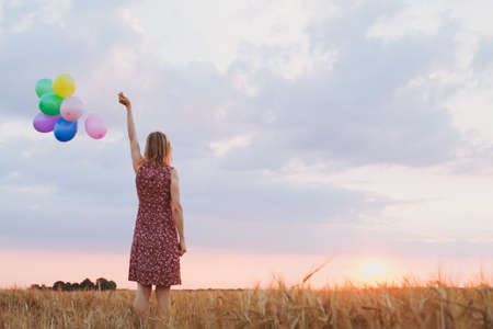 hope concept, emotions and feelings, woman with colourful balloons in the field, background 스톡 콘텐츠