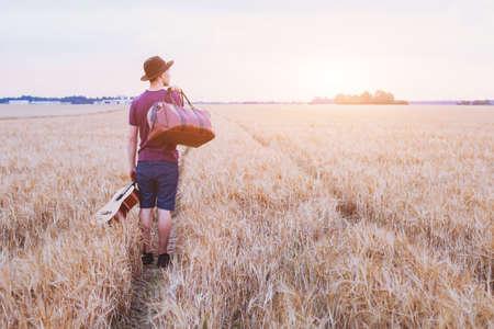 jonge zoon verlaten van huis, romantische reizen achtergrond, man met gitaar en road bag lopen bij zonsondergang veld Stockfoto