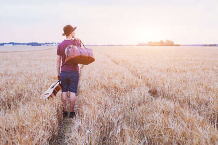 young son leaving home, romantic travel background, man with guitar and road bag walking at sunset field