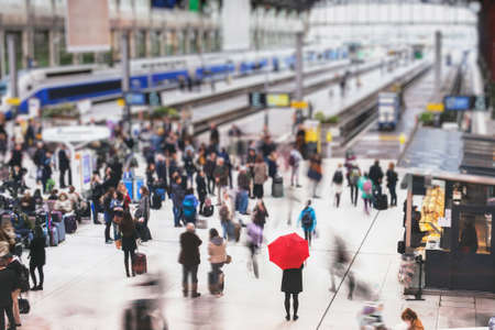 Vrouw met rode paraplu, wachten op treinstation en wazige mensen in beweging, eenzaamheid concept
