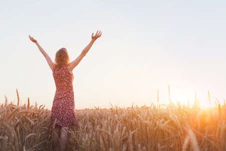 呼吸は、フィールドでの夕日を楽しむ挙手を持つ女性 写真素材