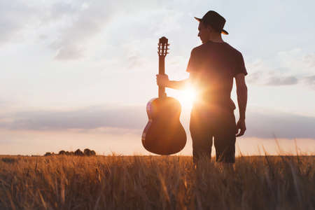 silhouette of musician with guitar at sunset field Stock Photo