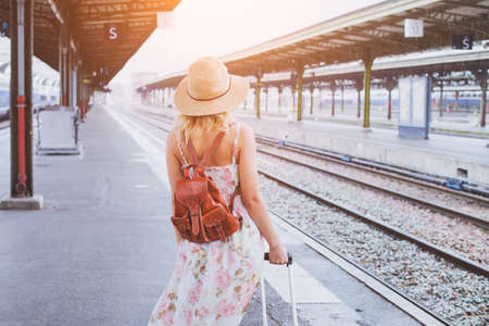 summer travel, woman with suitcase waiting for  her train on platform of railway station 版權商用圖片 - 77338725