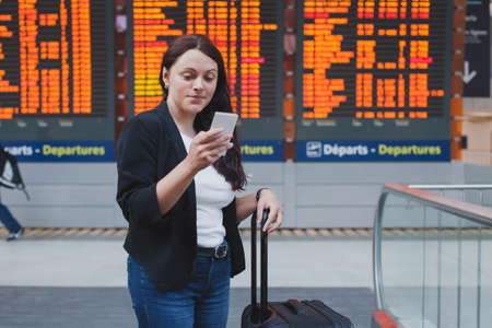 woman with smartphone in international airport checking timetable of the flight