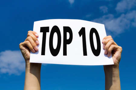 top 10, hands holding sign in blue sky Stock Photo