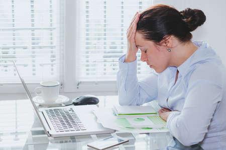 vermoeide zakenvrouw met computer op kantoor, stress en problemen, spijt en schuldig voelen