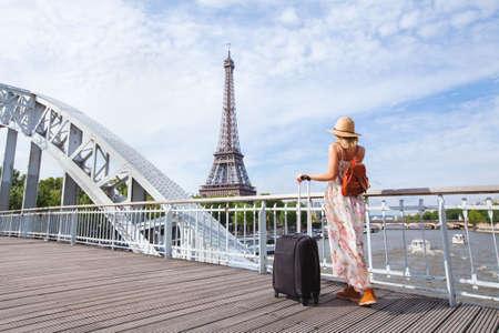 パリ、ヨーロッパ ツアー、フランスのエッフェル塔近くのスーツケースを持つ女性への旅行します。