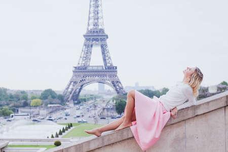 romantic girl in Paris, fashion woman looking up near Eiffel tower