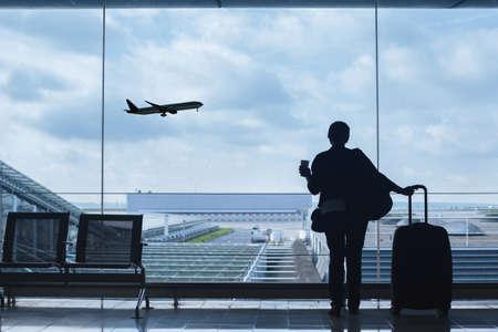 reiziger op luchthaven kijken naar het opstijgen van het vliegtuig Stockfoto