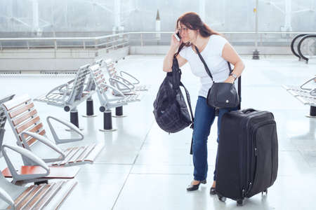 많은 가방과 수하물로 공항에있는 고민 된 여성을 강조했습니다.