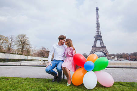 photo shoot, happy couple with balloons posing near Eiffel tower in Paris