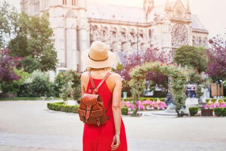 パリ、フランスのノートルダム大聖堂近くのバックパックと観光に移動する美しい女性のファッション