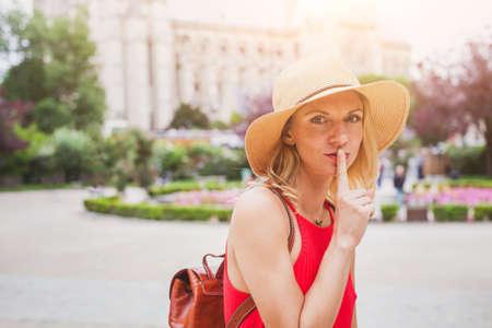 secret concept, finger on the lips, portrait of woman traveling Stock Photo