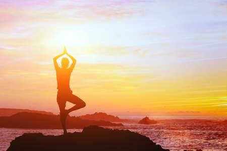 beautiful yoga background, silhouette of woman on the beach at sunset, mindfulness Reklamní fotografie - 77334027
