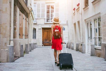 Viajes de fondo, mujer turística caminando con la maleta en la calle en la ciudad europea, el turismo en Europa Foto de archivo