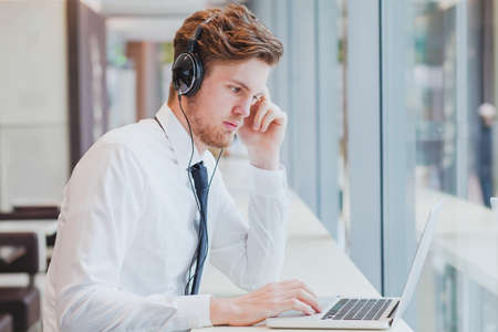 hear business call: businessman in headphones working with laptop in modern cafe interior Stock Photo
