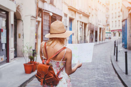travel guide, tourism in Europe, woman tourist with map on the street Foto de archivo