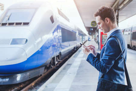 man using mobile application on his smartphone at train station, business travel Stockfoto
