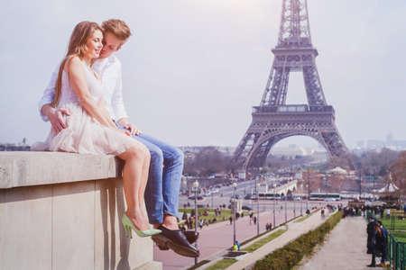 kiss love: romantic love, affectionate couple sitting near Eiffel Tower in Paris, honeymoon in Europe Stock Photo