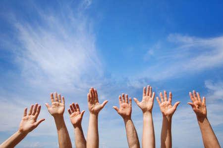 자원 봉사의 개념, 푸른 하늘에 사람들이 자원 봉사자의 그룹의 손 스톡 콘텐츠
