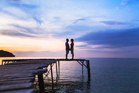 Beautiful romantic love background, silhouette of affectionate couple on the pier at sunset beach Stock Photo