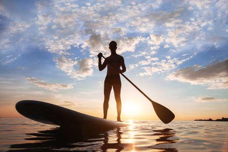 Paddle standing, silhouet van man op het strand bij zonsondergang