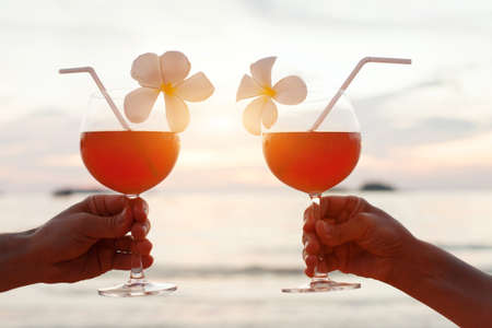 Celebración de luna de miel en la playa, pareja animando con cócteles tropicales al atardecer Foto de archivo - 77348327
