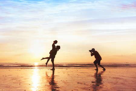 Photographe travaillant avec couple sur la plage, photographie de mariage professionnel Banque d'images - 77348195