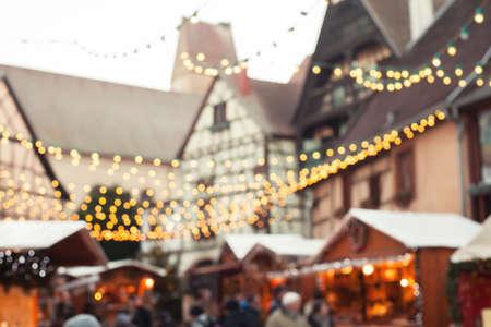 Kerstmarkt wazig achtergrond, mensen lopen in gezellige ingerichte straat met garlandes en houten huizen van winkels